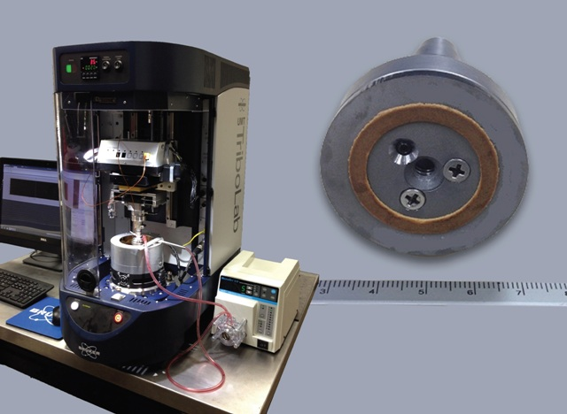 The UMT TriboLab benchtop tribotest system used in the simulation of clutch material testing, and detail of sub-scale clutch material sample (ruler in cm).