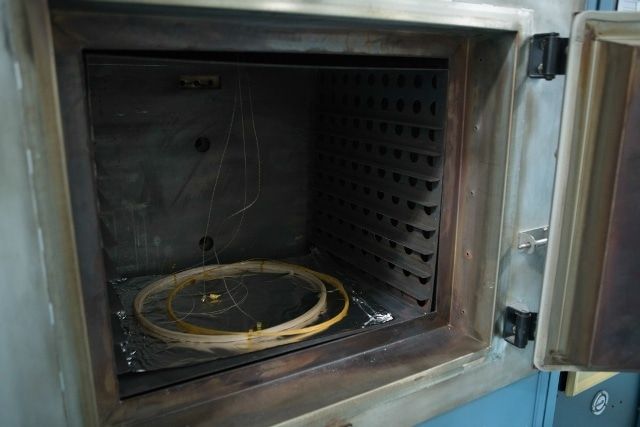 Testing scheme for elevated temperature cycling measurements showing placement of fiber optic coils in the furnace.