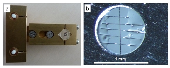 a) Photography of the T-Tool developed at HMI/HZB, with a glass cylinder attached to it, on top of which the specimen is clued by use of hot wax. b) Light micrograph of the inner part of a Mo support ring, showing the interface region (black vertical line in the middle of the image) with the glass substrates of the thin-film stacks on either side, as well as carbon fibers glued across the interface region of the cross-section.