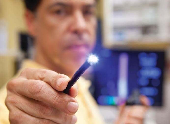 A doctor holds a lighted probe used in endoscopic procedures.