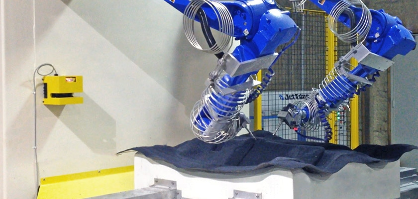 Alliance Automation's 6-axis robotic waterjet trimming cell with dual wall-mounted Motoman HP20D robots powered by Jet Edge's 60KSI (4100) bar iP60-50 intensifier.