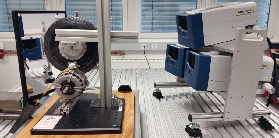 Laboratory Setup. The three Vibrometer Sensor Heads are mounted to a common frame (right side). The roller test bench is to the left with the tire on top and the motor on the bottom. The mirror on the far left is used to simplify the repositioning of the vibrometer scan pattern.