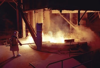 A furnace operator takes a sample before pouring the liquid aluminum oxide.